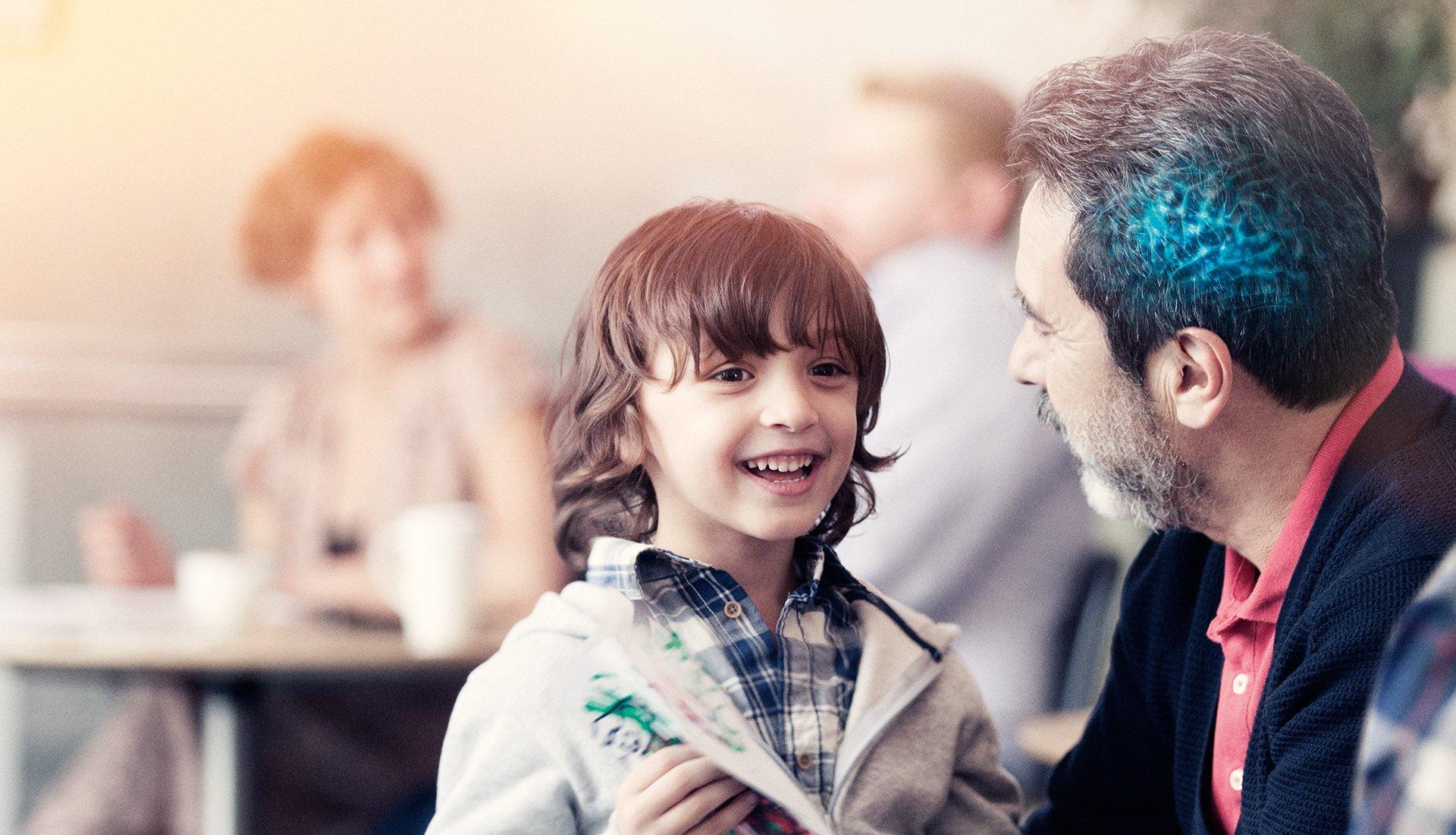 jeune garçon avec son papa dont le cerveau est illuminé en bleu brainhearing oticon