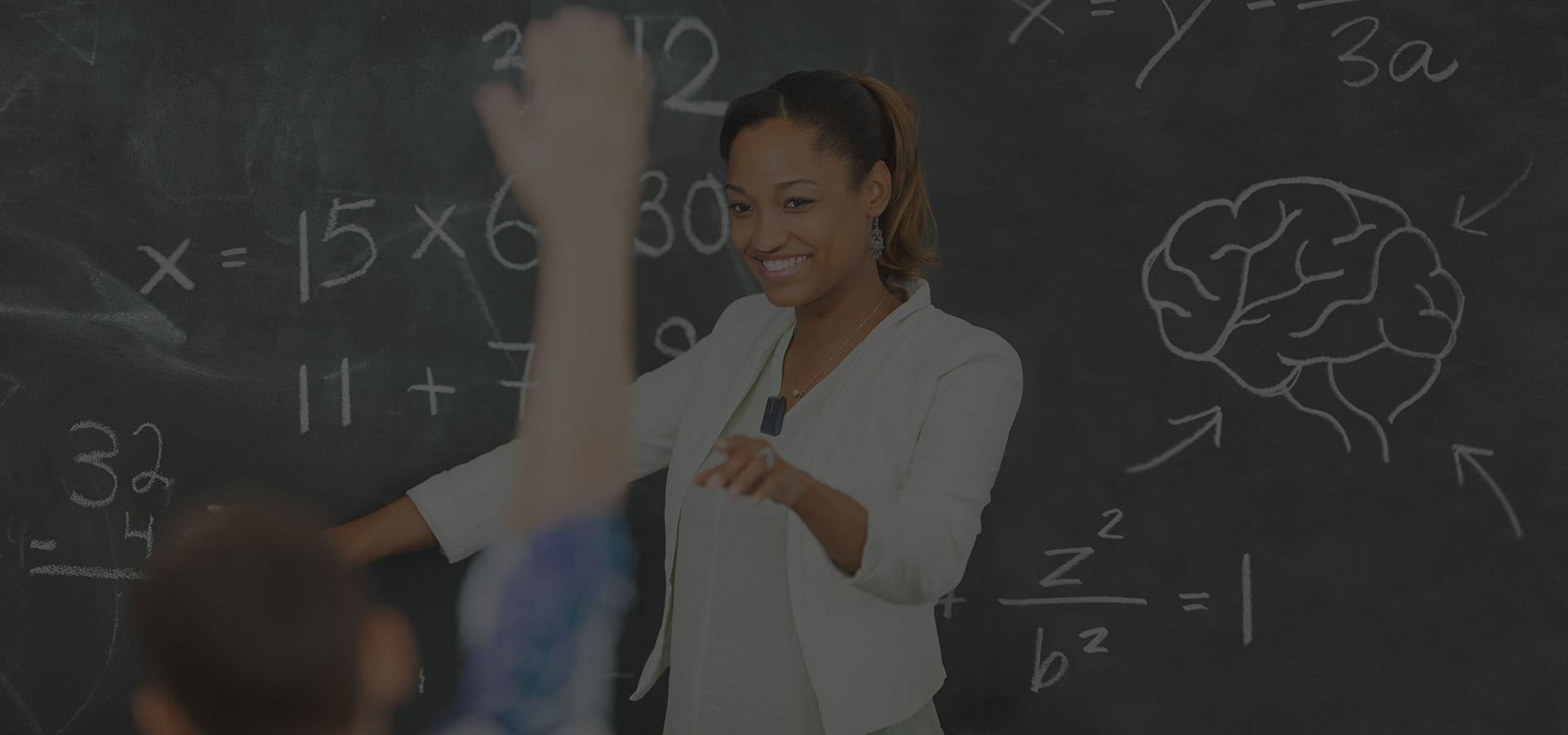 Teacher standing by the blackboard