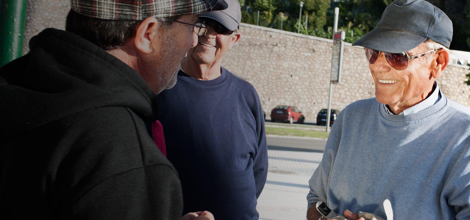 trois hommes âgées seniors avec casquettes parlent ensemble