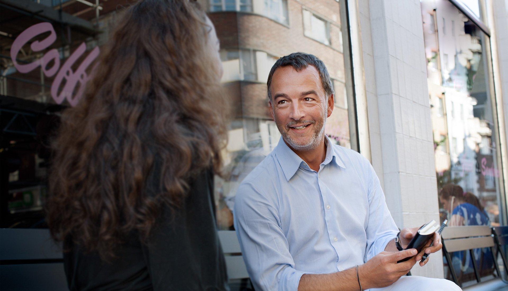 homme et femme de dos parlant dans la rue adossés à une vitrine
