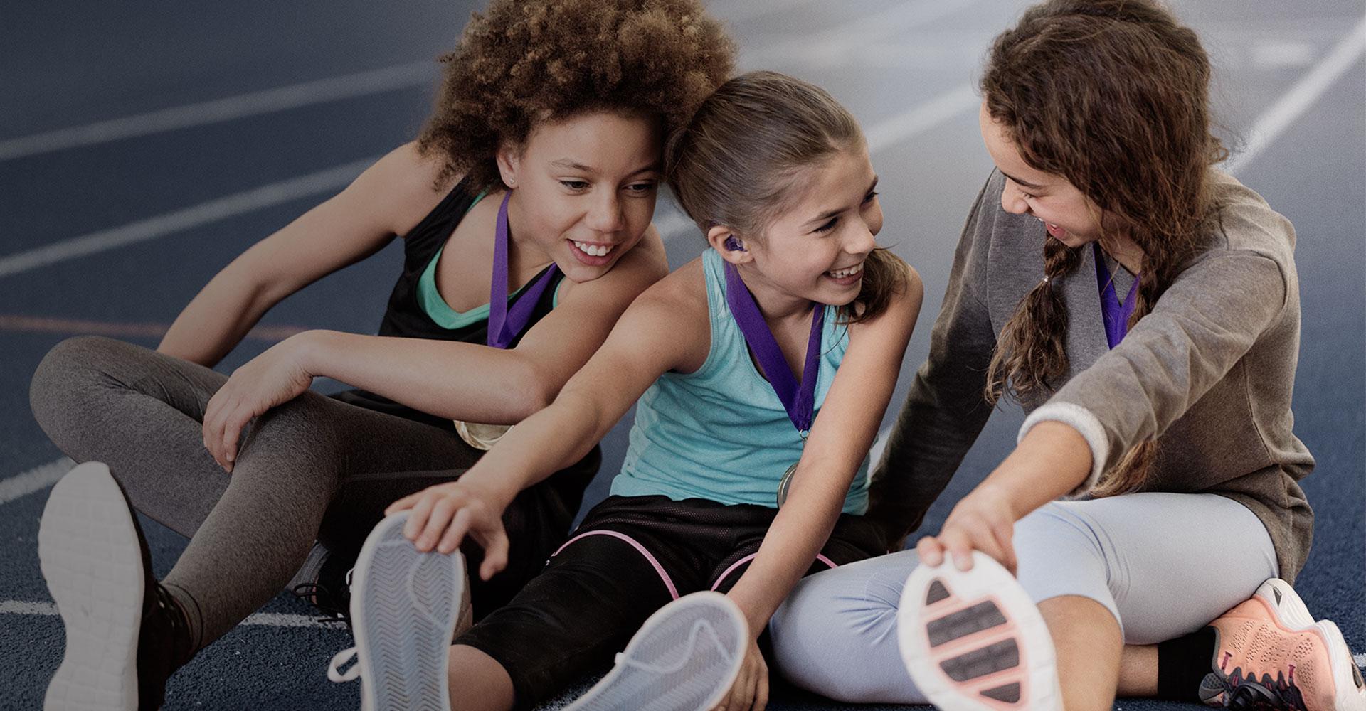 3 jeunes filles en train de s'amuser dans un gymnase faisant du sport