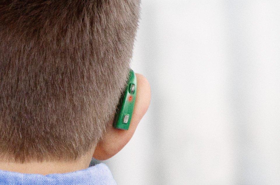 gros plan de dos oreille enfant avec appareil auditif vert