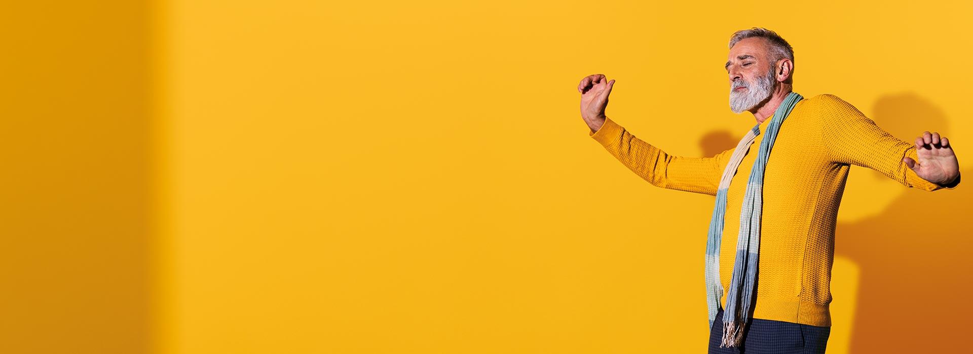 Ein Mann mittleren Alters, der Philips HearLink Hörgeräte trägt, tanzt und fühlt sich selbstbewusst.