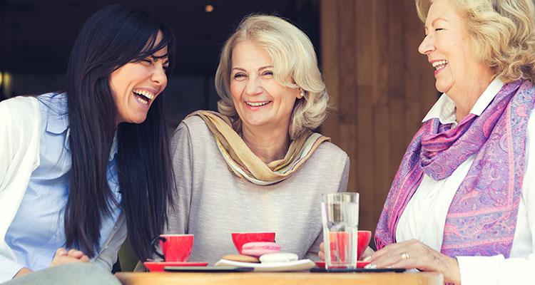 Drei Frauen, die es genießen, Zeit in einem Café im Freien zu verbringen und sich ohne Schwierigkeiten unterhalten.