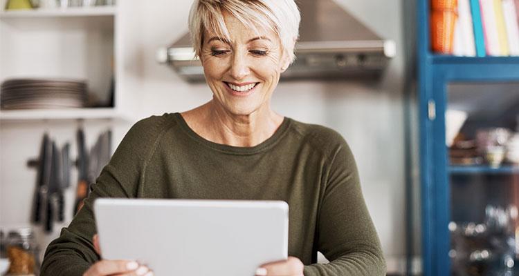 Frau in den Fünfzigern, die einen Online-Hörtest auf ihrem Tablett macht, während sie zu Hause ist.