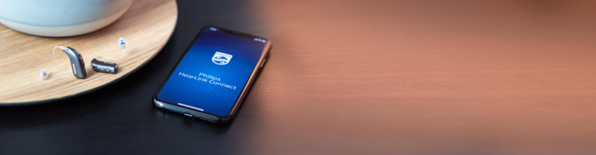Philips HearLink Hörgeräte neben einem Smartphone, das auf dem Display die Philips HearLink Connect App anzeigt.