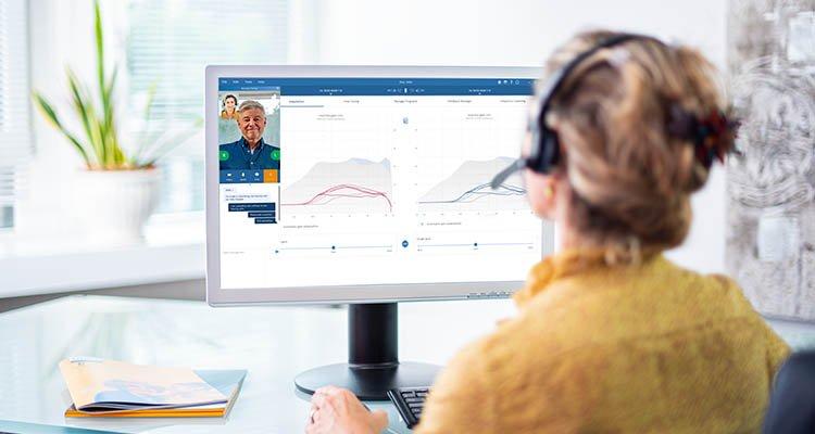 Hörgeräteakustiker bei einem online Remote Fitting Termin mit einem Philips HearLink Träger.