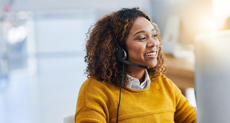 Frau, die am Telefon spricht und einem Kunden hilft.
