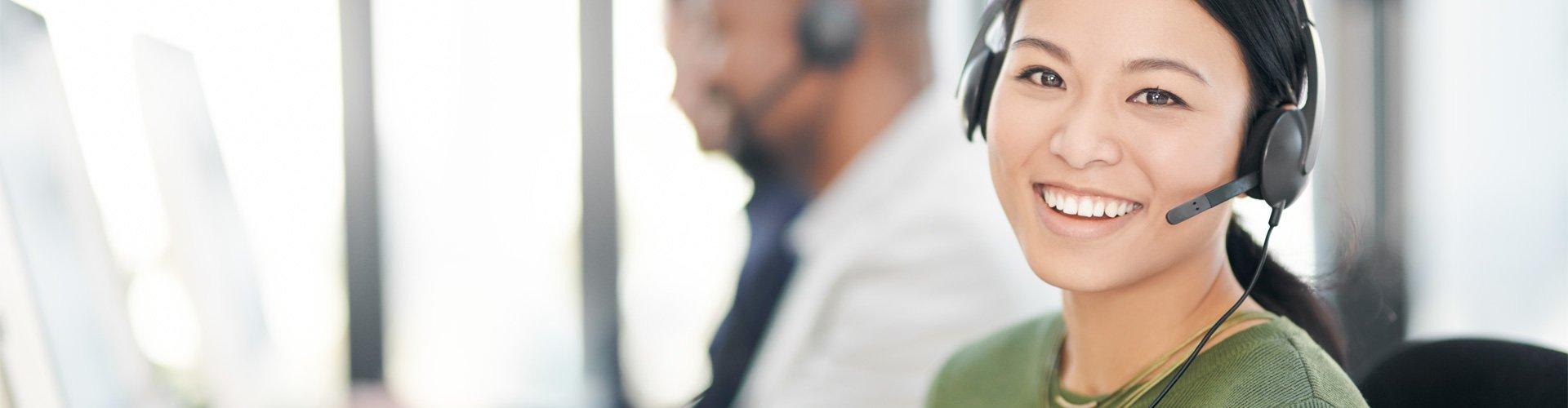 Frau am Telefon, die einem Kunden mit ihren Hörgeräten hilft.