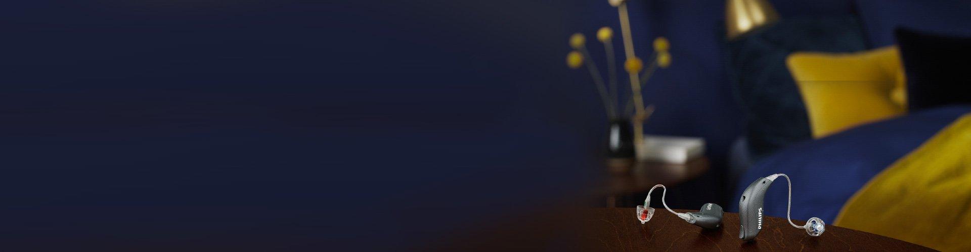 Ένα ζευγάρι miniRITE ακουμπισμένα στο κομοδίνο δίπλα στο κρεβάτι. Ακούμε καλύτερα με βοηθήματα ακοής Philips HearLink.