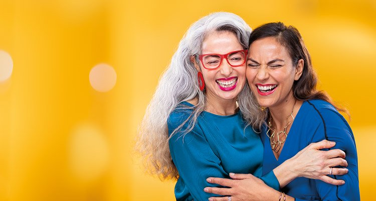 Two middle-aged women hugging each other. One is wearing Philips HearLink miniRITE T hearing aids.