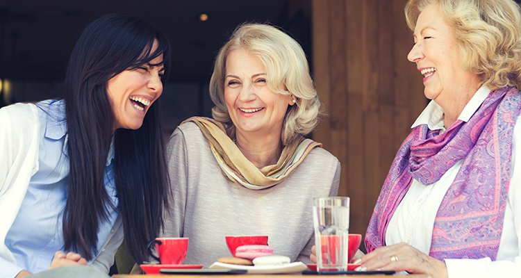 Three women enjoying spending time in an outdoor café and having a conversation without difficulties understanding each other
