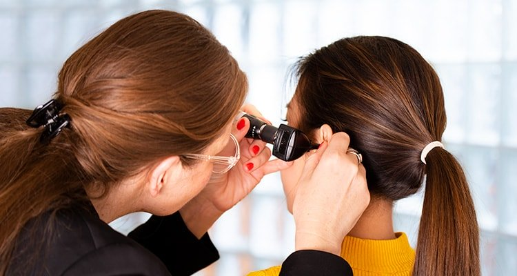 A hearing care professional is looking with an otoscope into the ear canal of a patient