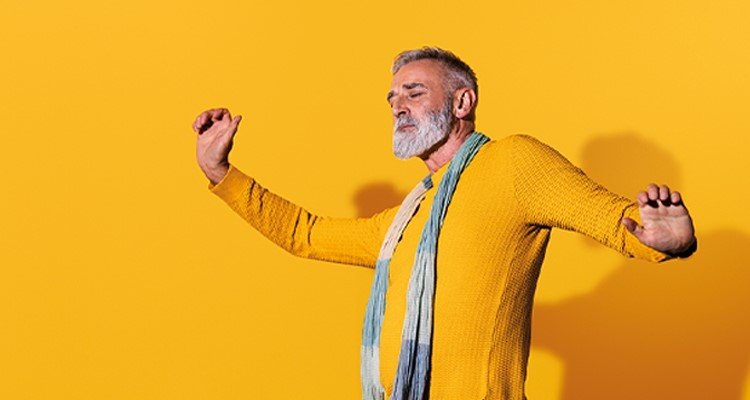 Middle aged man wearing Philips HearLink hearing aids is dancing and feeling self conficent.