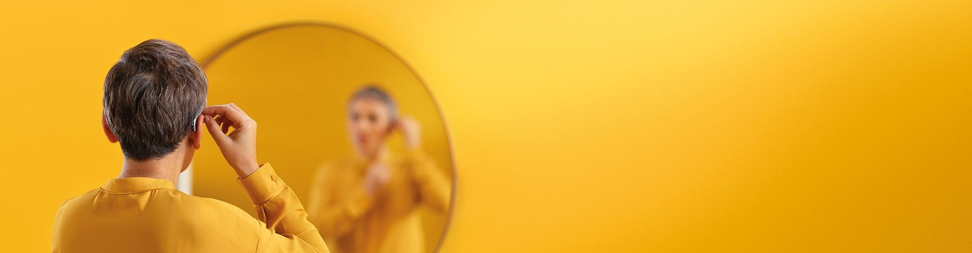 Mujer poniéndose su audífono Philips. Philips HearLink cuenta con una gama de estilos de audífonos.