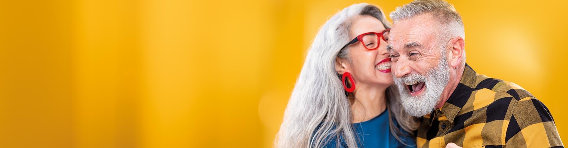 Una mujer de mediana edad abrazada y susurrando un secreto a un amigo. Él lleva audífonos recargables Philips HearLink.