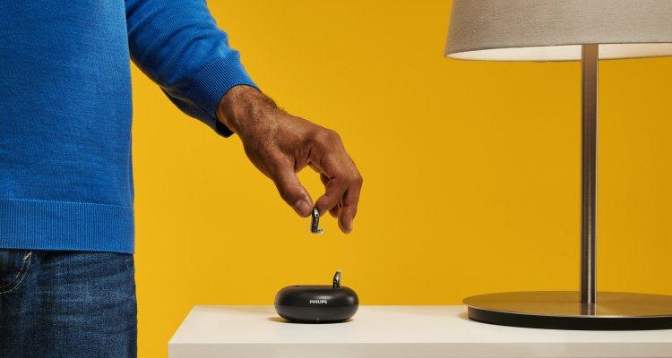 Hombre poniendo sus audífonos recargables Philips HearLink en el cargador. 3 horas de carga para un día completo de audición.