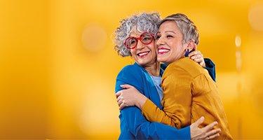 Dos mujeres de mediana edad abrazándose. Uno está usando aparatos auditivos Philips HearLink en el oído casi invisibles.