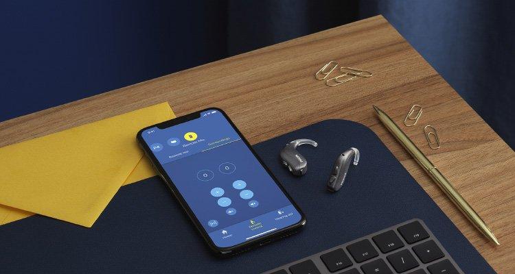 Aparatos auditivos Philips HearLink BTE PP junto a un teléfono inteligente con la aplicación Philips HearLink abierta.