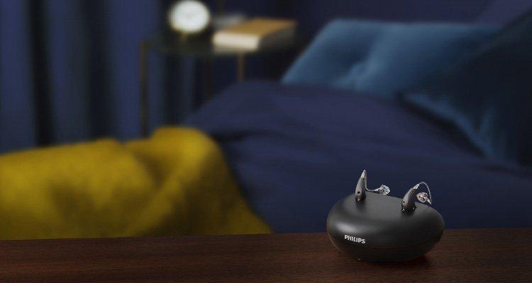 Aparatos auditivos recargables Philips HearLink miniRITE T R en el cargador en una mesa en un dormitorio.