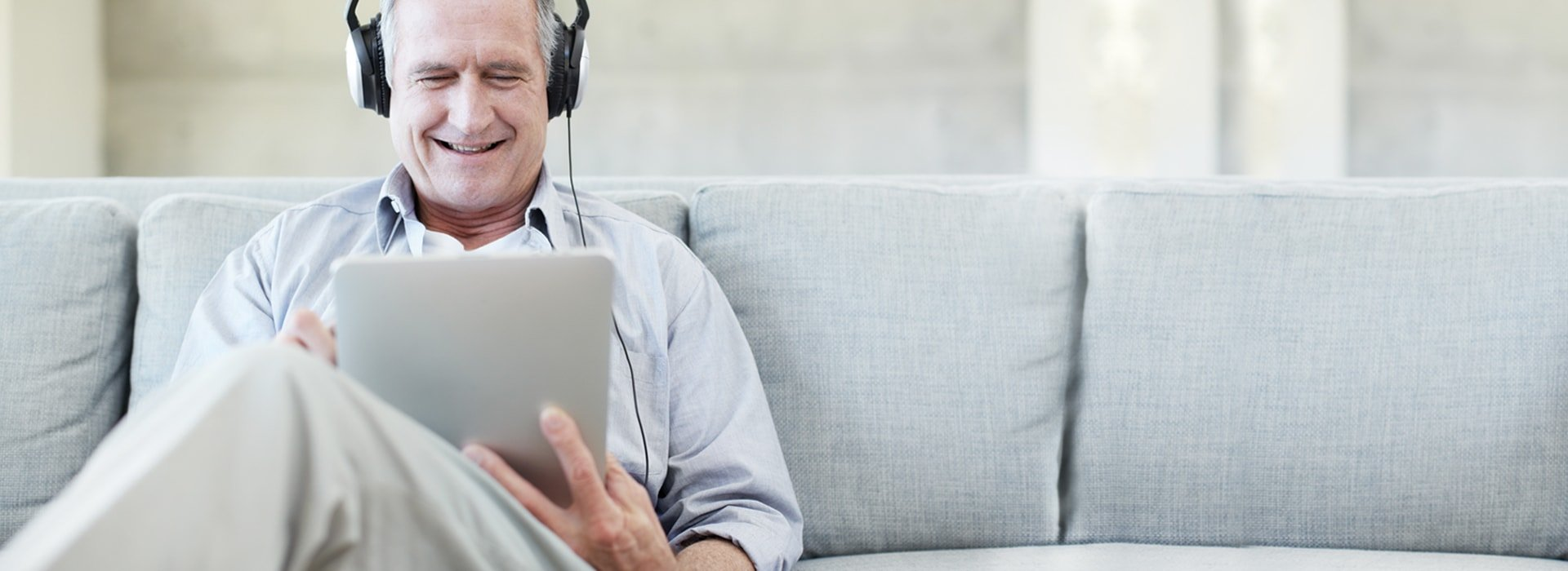 Hombre sentado en el sofá comprobando su audición con la prueba de audición en línea.