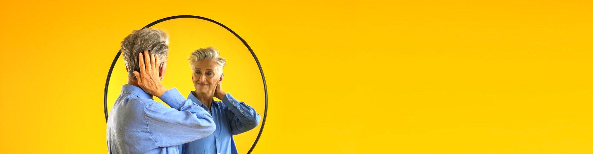 Une femme souriante qui porte un appareil auditif Philips HearLink et qui se regarde dans le miroir
