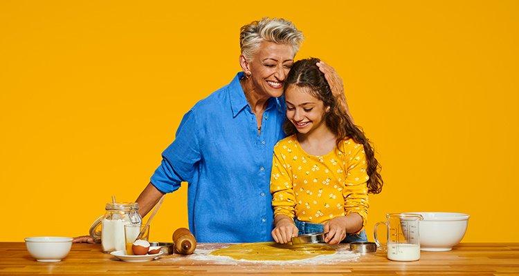 Une grand-mère moderne qui porte un appareil auditif Philips HearLink et qui profite d'un moment précieux avec sa petite-fille en cuisinant des gâteaux