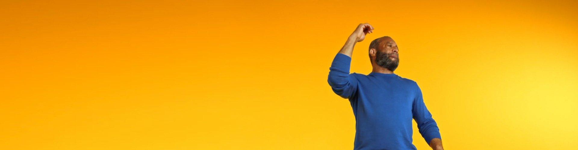 Un homme qui porte des appareils auditifs Philips et qui passe un bon moment en écoutant de la musique et en se connectant à ses proches.