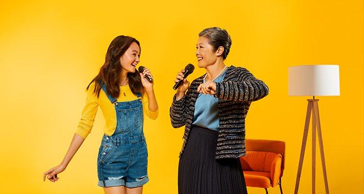 Une tante qui porte des appareils auditifs Philips HearLink et qui change du karaoké avec sa nièce en profitant pleinement de la musique