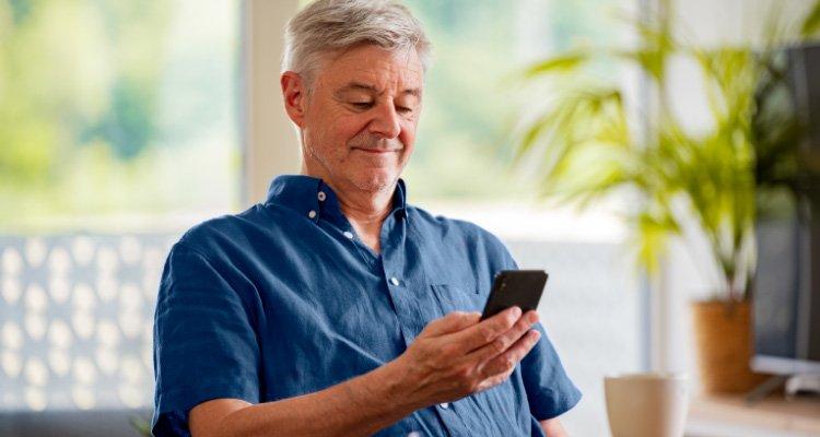 Un utilisateur d'appareils auditifs Philips qui se connecte à un rendez-vous avec son smartphone connecté à l'application Philips HearLink Connect.