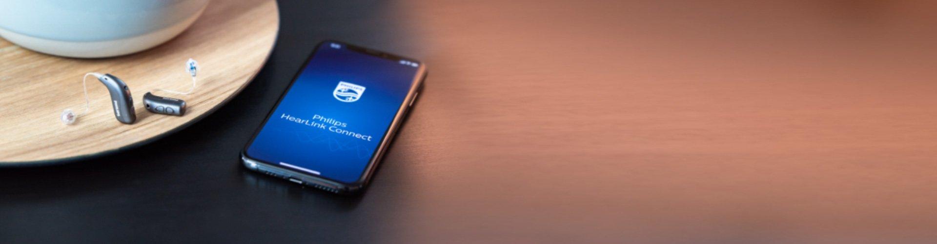 Des appareils auditifs Philips HearLink posés à côté d'un smartphone avec l'application Philips HearLink Connect ouverte.