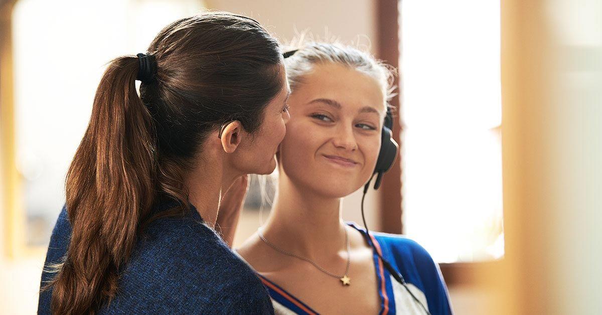 Mère avec des appareils auditifs embrasse sa fille