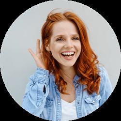 une jeune femme aux cheveux roux tient sa main à l'oreille