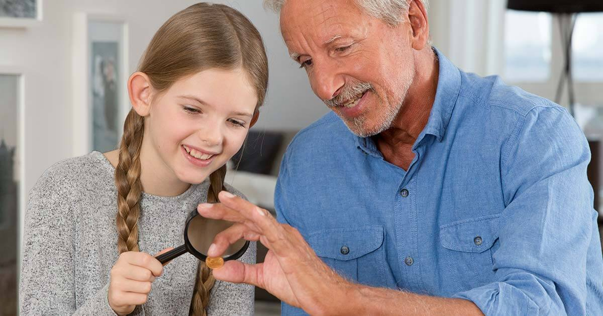Grossvater mit Enkelin schauen sich Goldmuenzen an