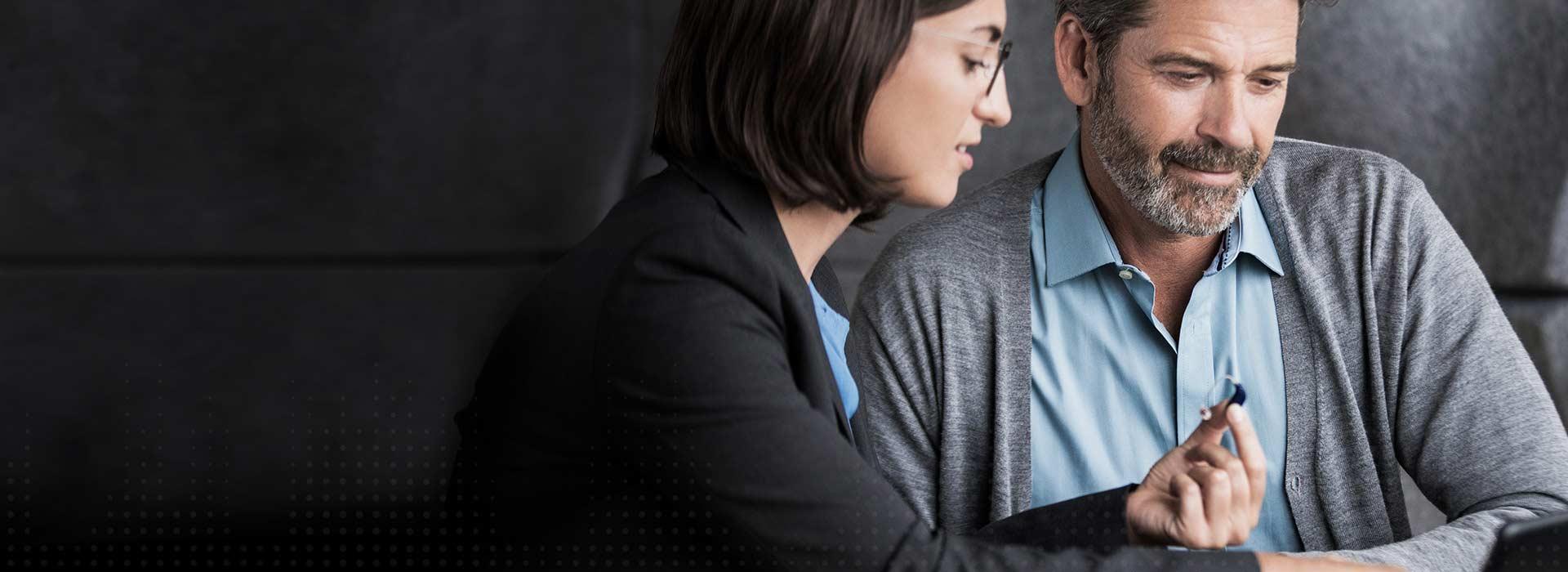 Un homme s'assoit avec une audioprothésiste et regarde l'Oticon Opn