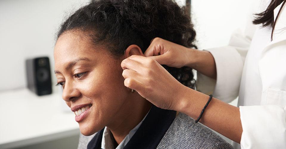 Une femme essaie des appareils auditifs