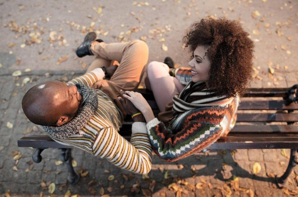 Un jeune couple assis sur un banc dans le parc