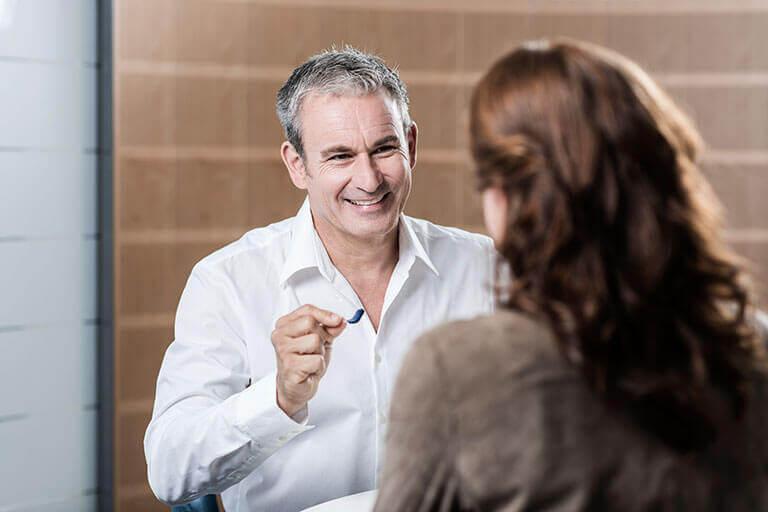 Un audioprothésiste montre au client un appareil auditif