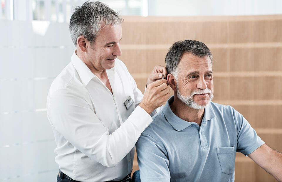 L'audioprothésiste pose l'aide auditive sur l'oreille.