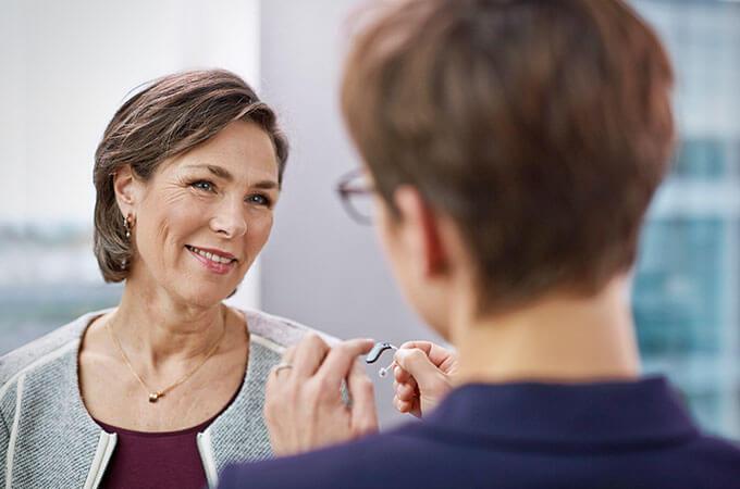Une audioprothésiste montre au client une appareil auditif