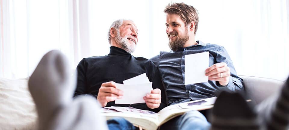 Le père et son fils adulte regardent de vieilles photos