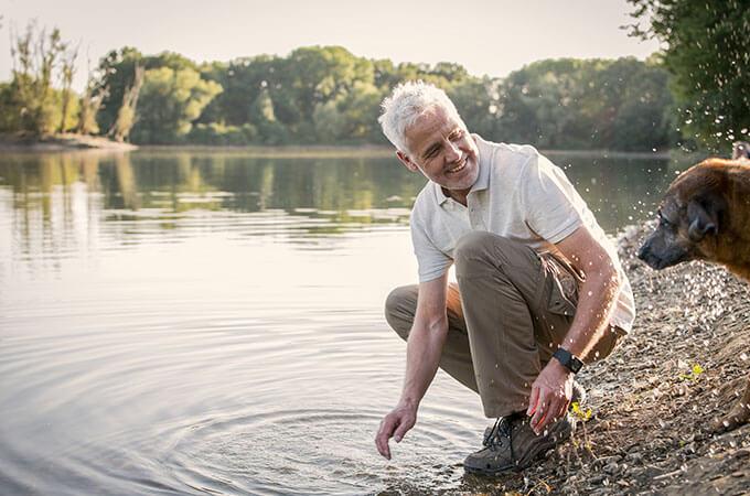 Homme avec un chien au lac