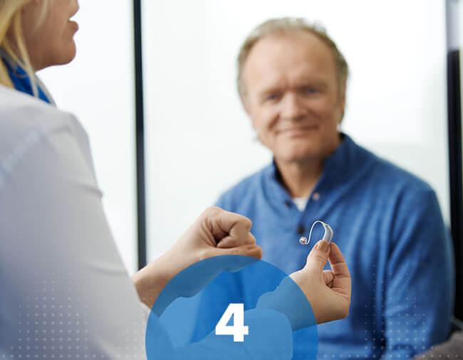 L'audioprothésiste montre une aide auditive