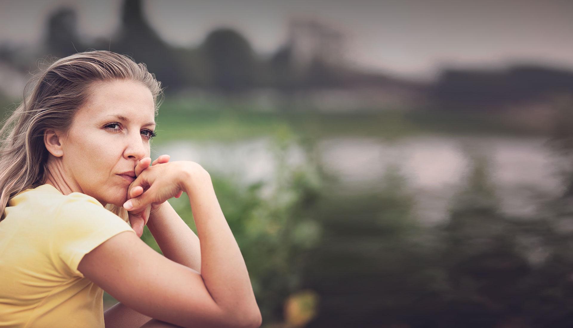 jeune femme au tee shirt aux cheveux blonds dans le vent à l'air pensif