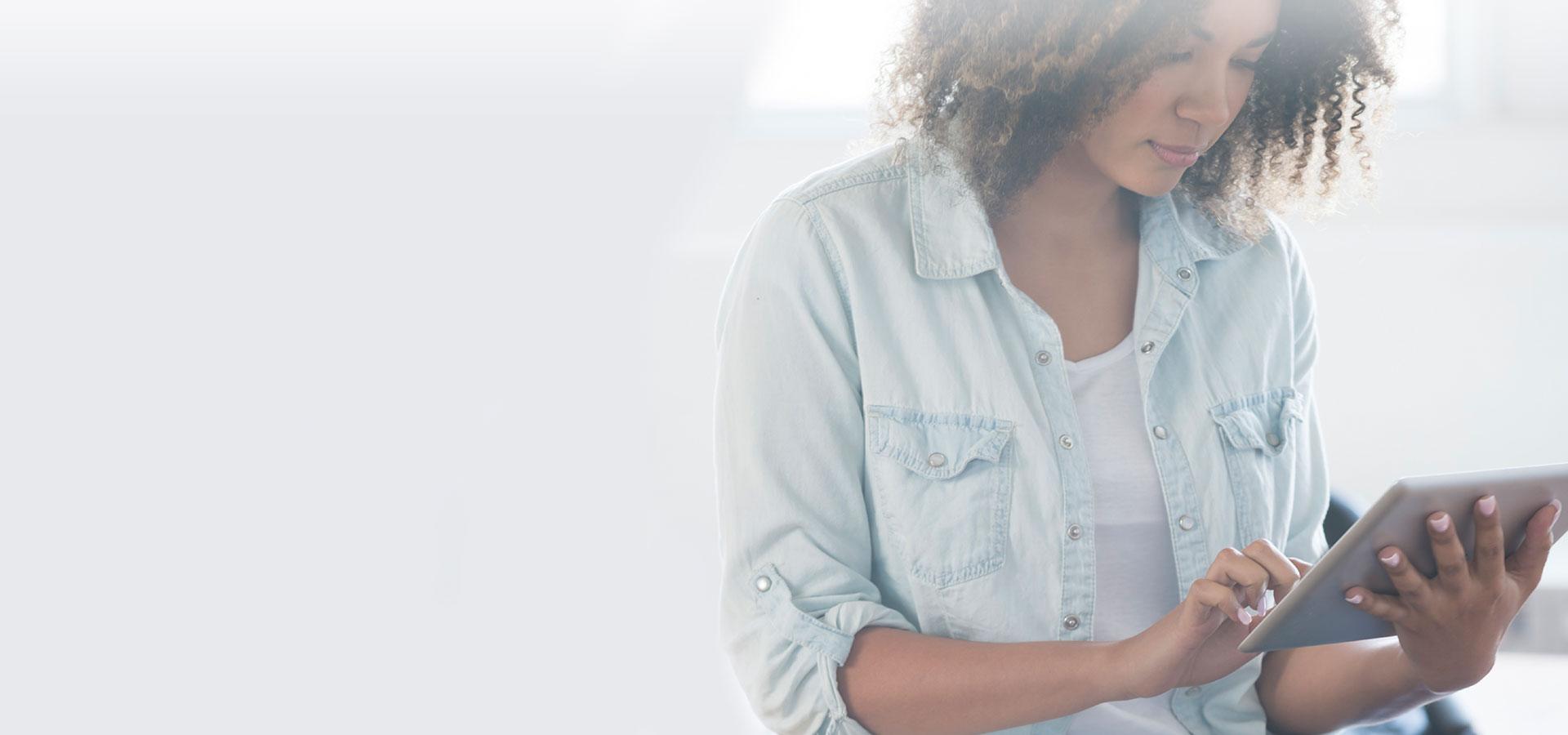 jeune femme metisse aux cheveux bouclés regarde un ipad, tablette numérique
