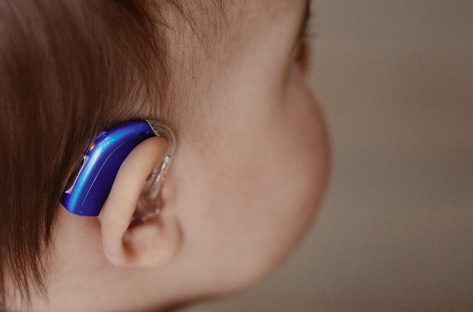 gros plan oreille de bébé avec appareil auditif bleu