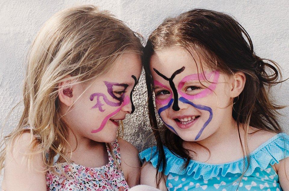 petites filles maquillées en papillons sur fond beige