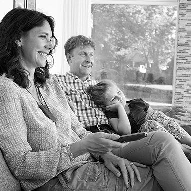 famille composée de la mère, le père et l'enfant, regardent la télévision dans leur salon en noir et blanc