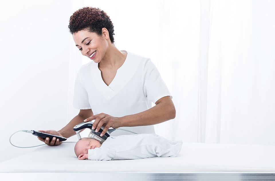 Audiologin macht einen Hörtest bei einem Baby mit Hilfe des easyScreen BERAphone Hörtestgeräts von MAICO. Die Mutter hält dabei das schlafende Kind.
