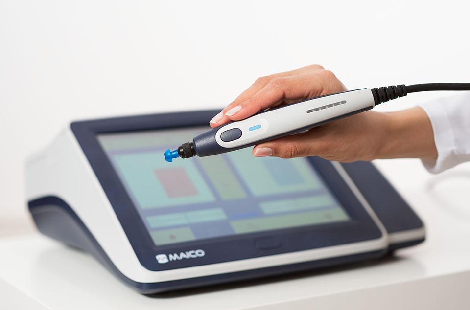 Hand mit Stiftsonde eines Tympanometers von MAICO